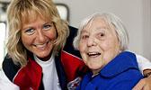 Foto: Pflegerin mit Seniorin - beide lachen.