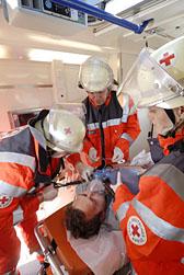Foto: Drei DRK-Helfer versorgen einen verletzten Mann auf einer  Tage in einem Einsatzfahrzeug.